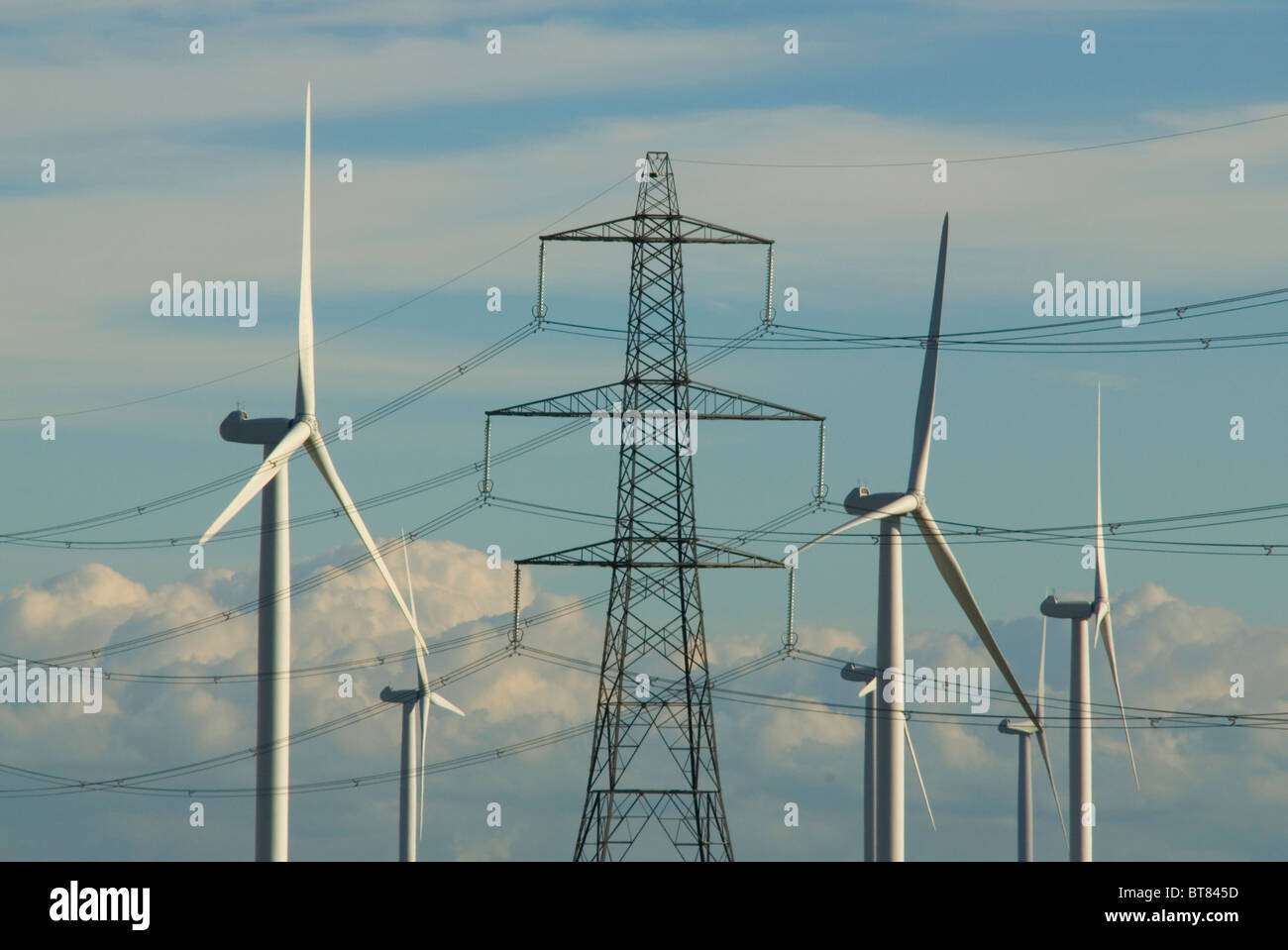 National Grid electricity transmission lines and pylons next to Nordex wind turbines at Little Cheyne Court wind - Stock Image