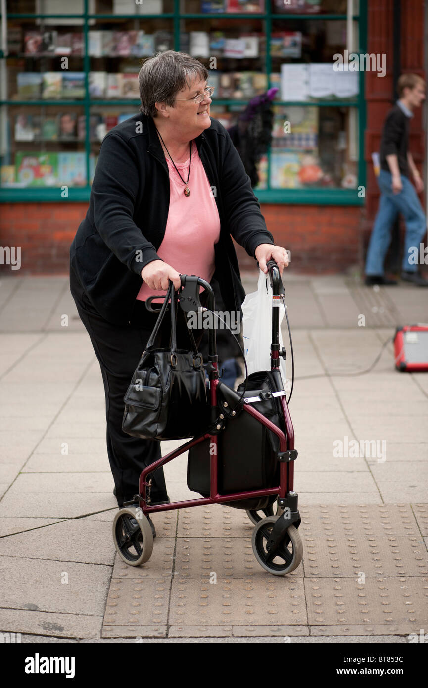 A middle aged woman using a three wheeled mobility aid 'Rollator' - Stock Image