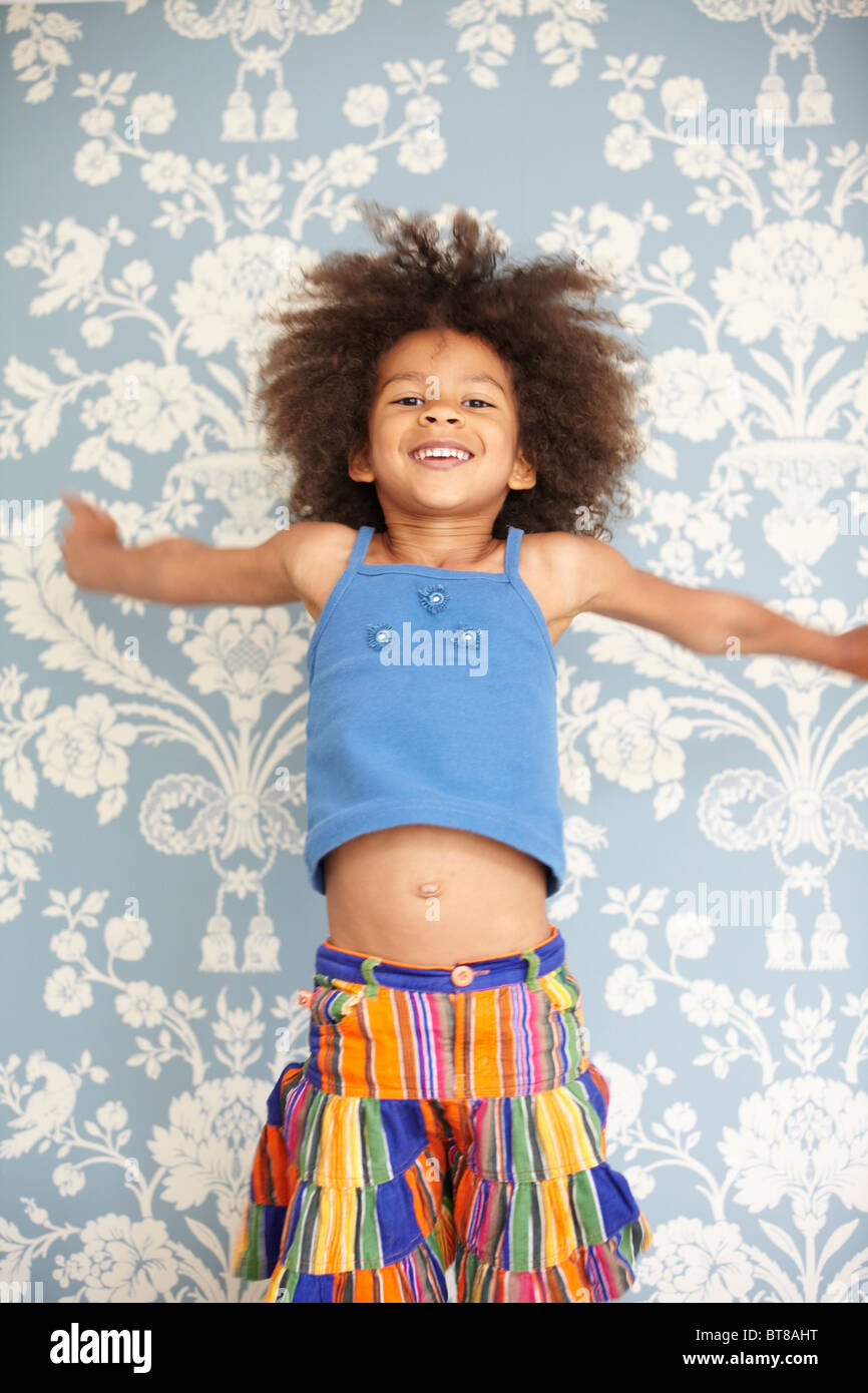 Young girl, mixed race child, jumping in the air in front of blue flowery wallpaper - Stock Image