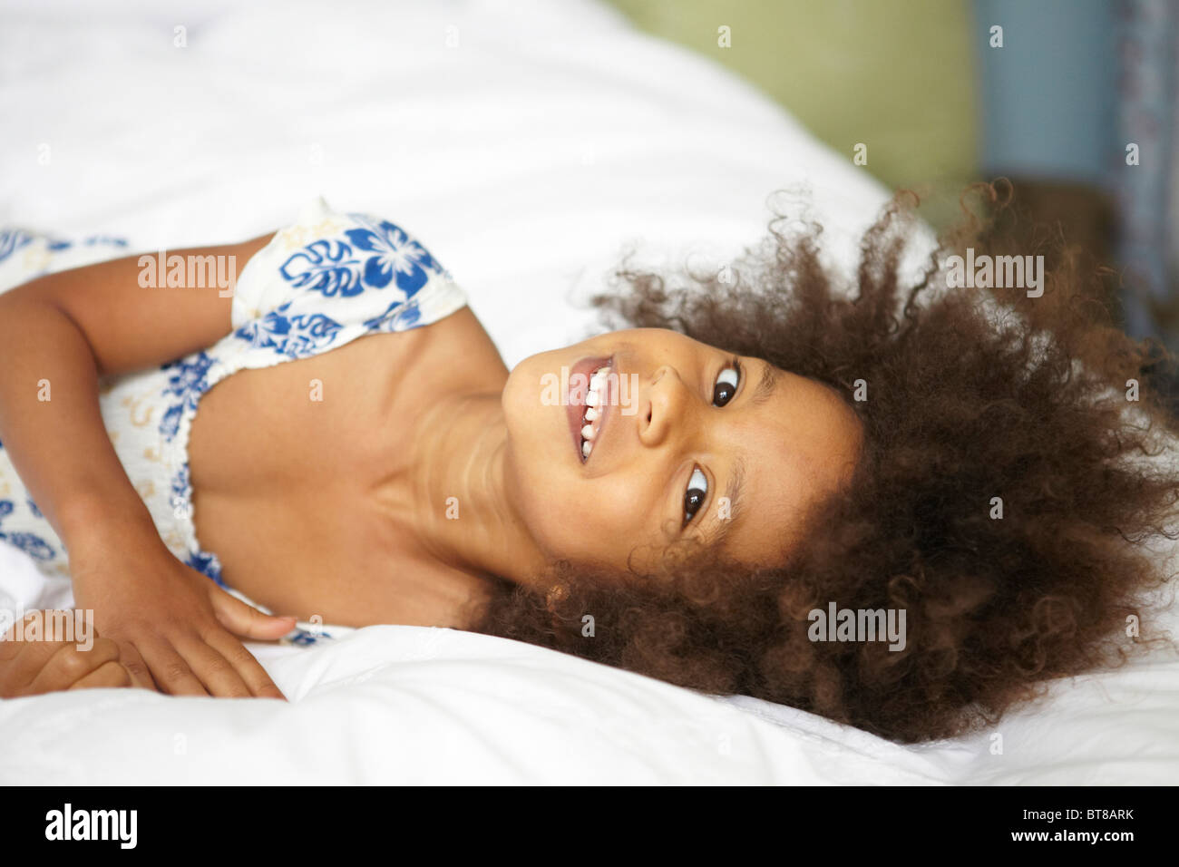 young mixed race girl, child laying on bed with white sheets in blue and white summer dress. Stock Photo