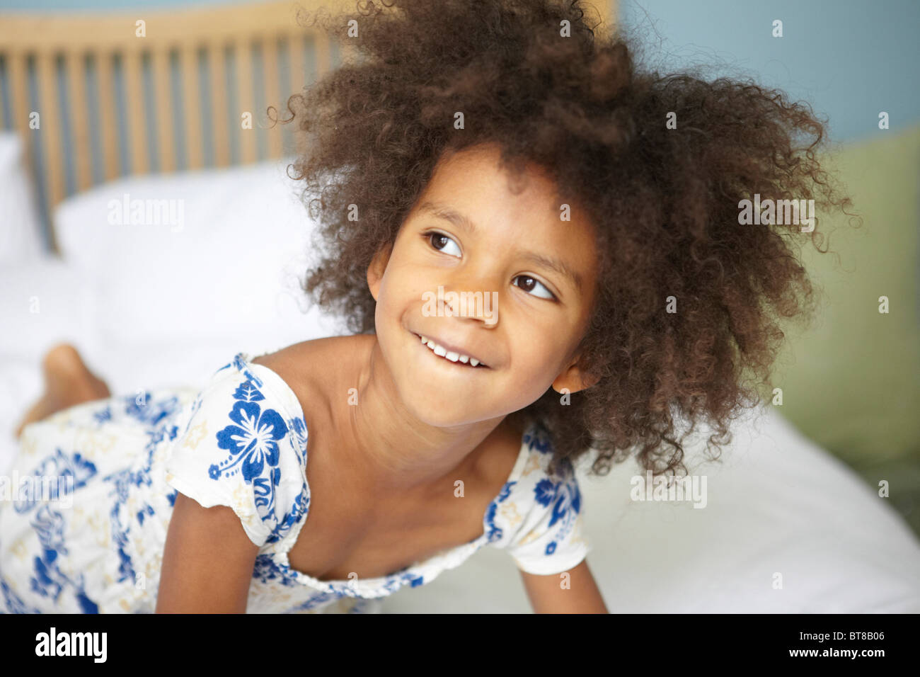 young mixed race girl (6) on bed looking mischievous in blue and white flower dress, leaning forward. - Stock Image