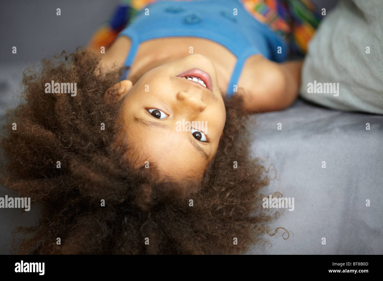 young girl, mixed race child, lying on grey sofa upside down, looking at camera - Stock Image