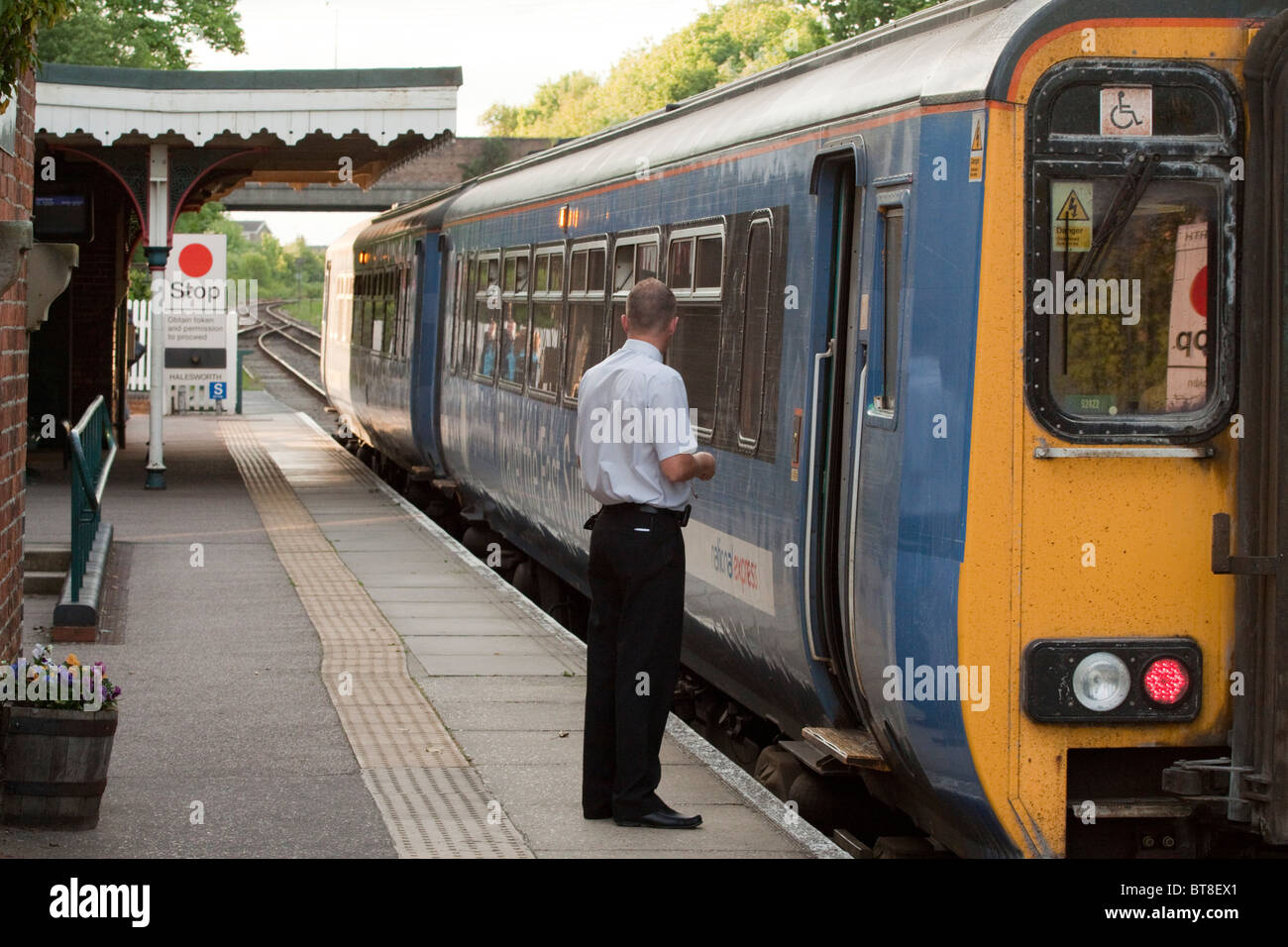 Guard of two coach local train checks empty platform at Halesworth station in Suffolk - Stock Image