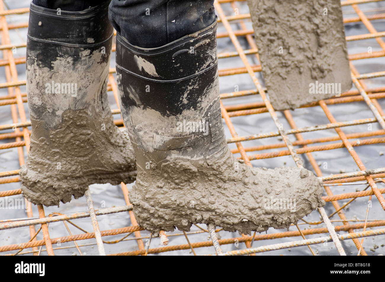 construction work worker concrete pore poring groundworker groundwork reinforced cast in situ foundation foundations - Stock Image