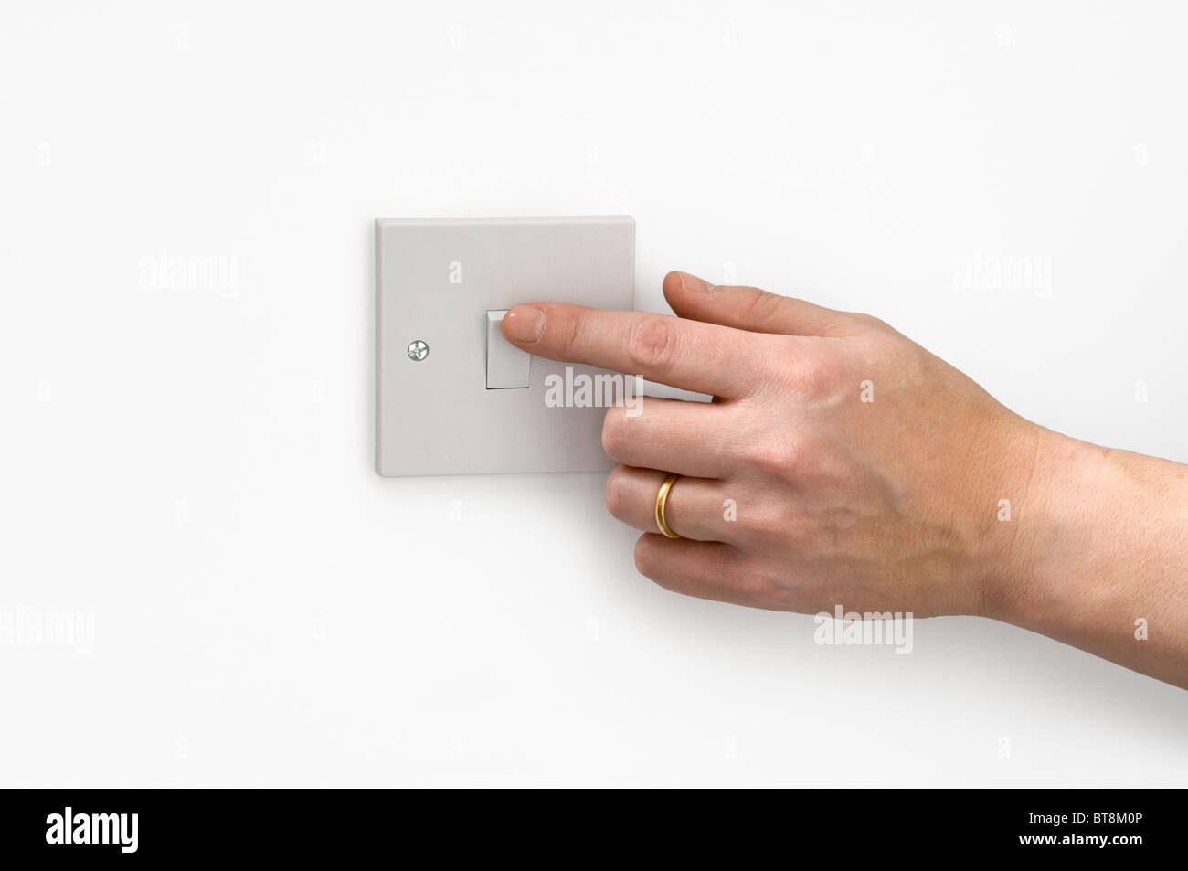 A hand operating a light switch. - Stock Image