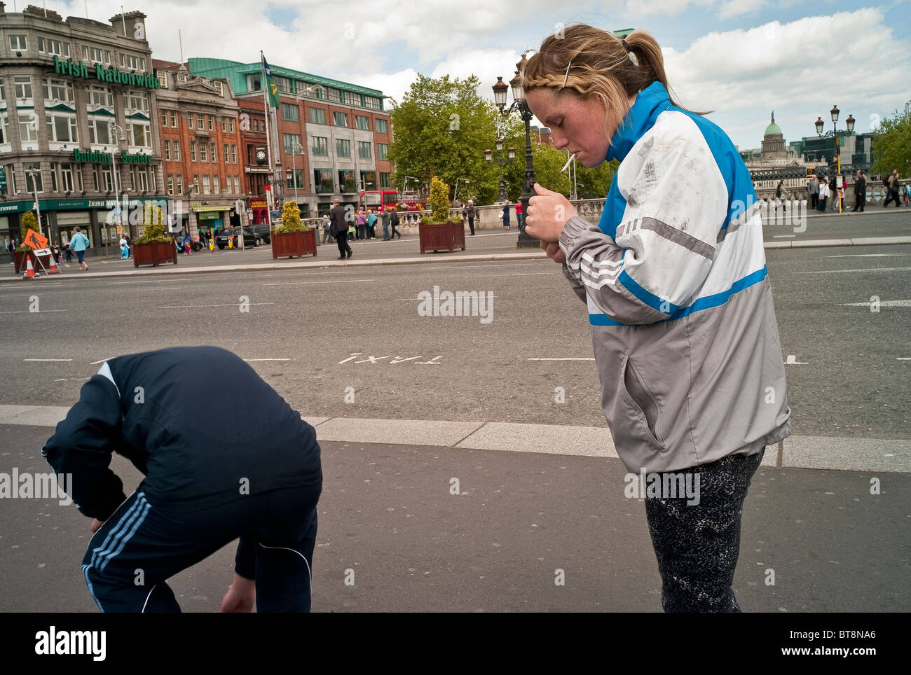 Young woman in Dublin on O'Connell bridge lighting a cigarette. A man bends over. - Stock Image