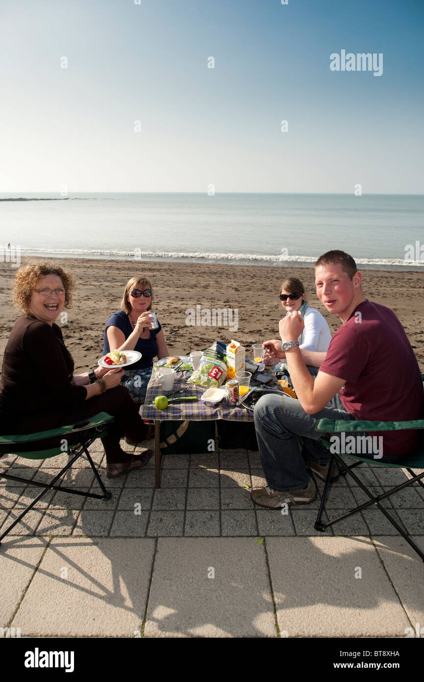 Sunny October afternoon - a family having an alfresco lunch picnic at the seaside, Aberystwyth wales UK - Stock Image