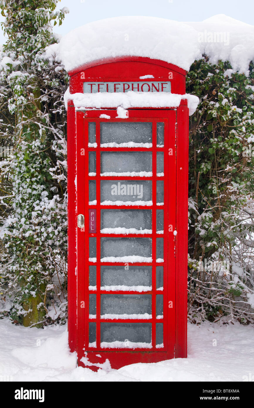 A traditional red British telephone kiosk in the snow at winter time. - Stock Image