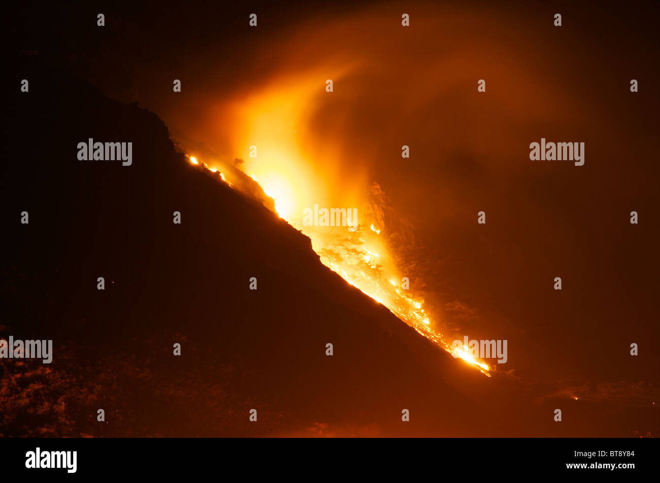 Wildfire at night in southern Crete burning ancient stone pines on mountainside location between Rodakino and Plakias - Stock Image