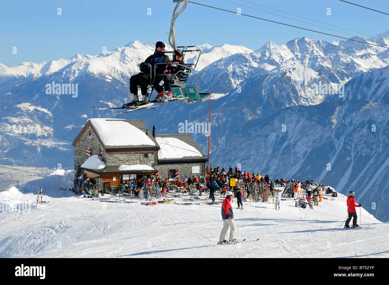 Skiers sitting on a chair lift hovering above the refuge Les Violettes in the Pennine Alps, Crans Montana, Valais, Stock Photo