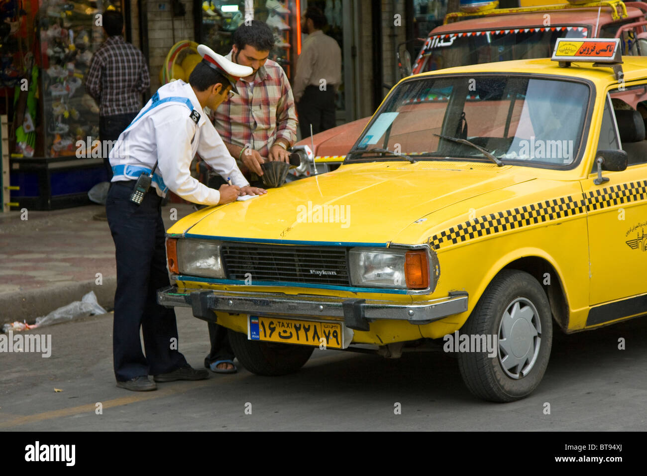 Policeman Issueing a Ticket to a Taxicab in Qazvin Iran - Stock Image