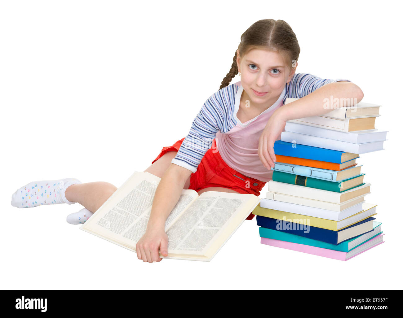 Girl sits having leant the elbows on a pile of books - Stock Image