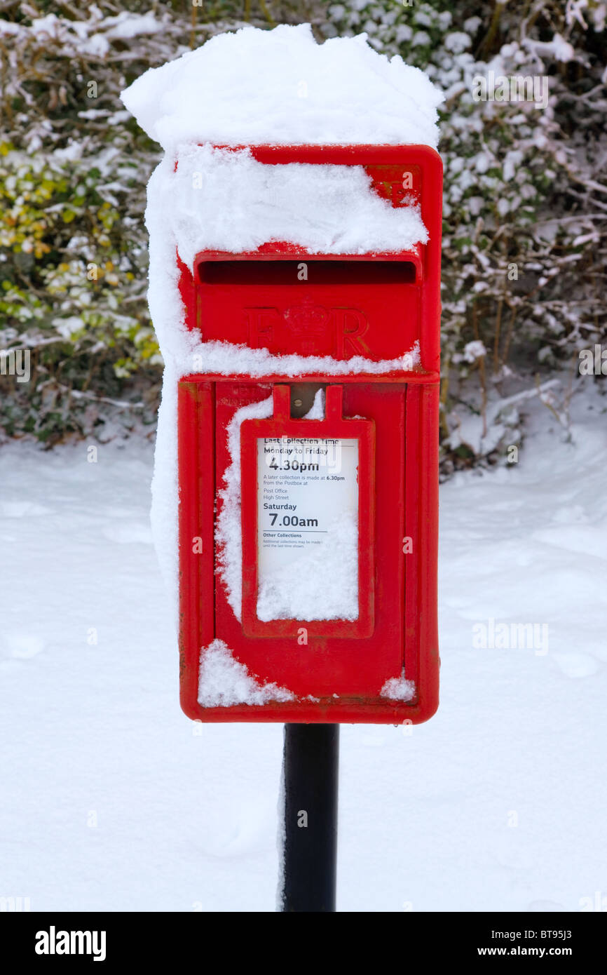 A traditional red English postbox at winter time covered in snow. - Stock Image
