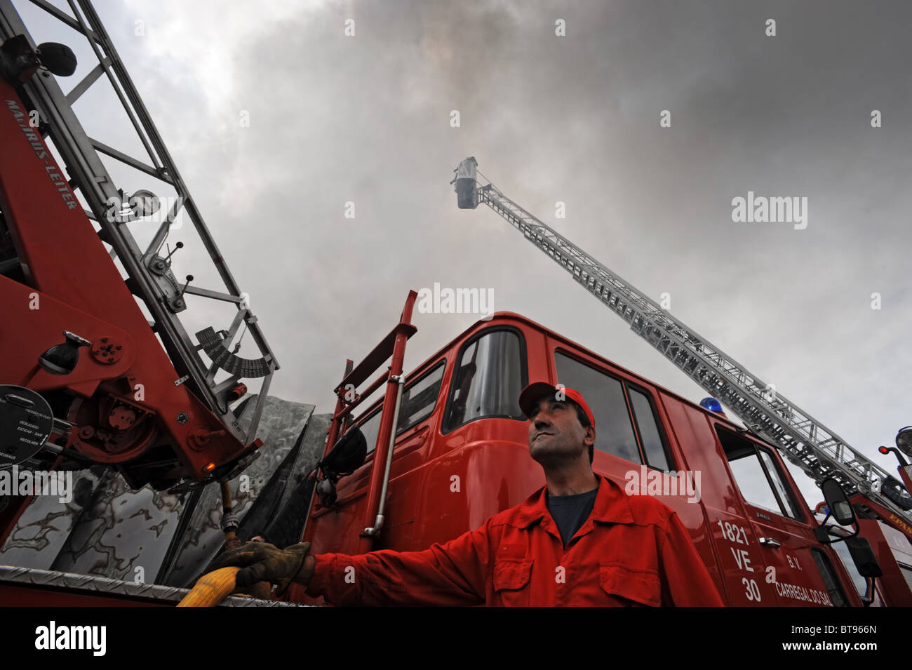 Fireman looking up next to a fire truck with an extension