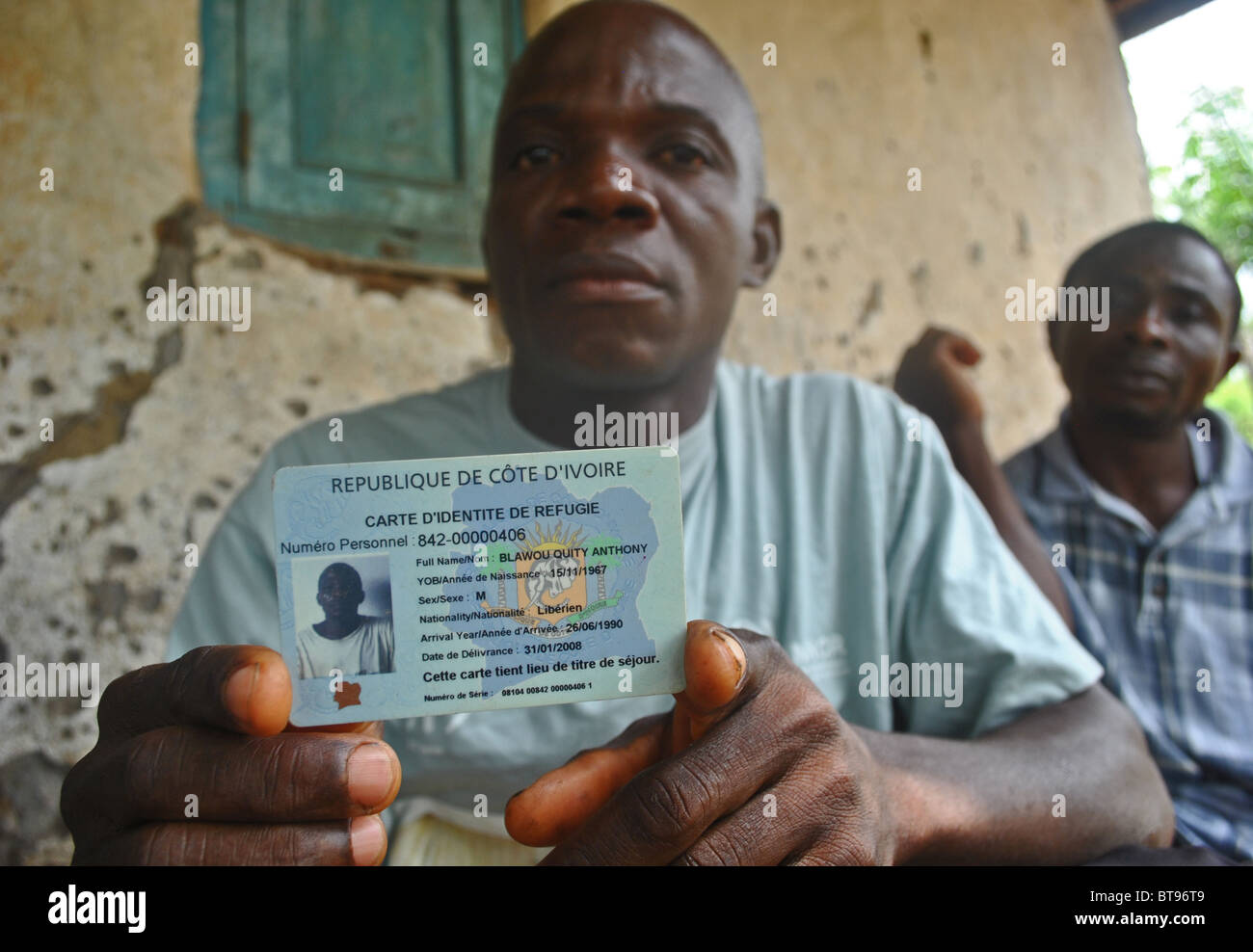 Liberian refugees display their refugee identity cards in Tabou, Ivory Coast, West Africa - Stock Image
