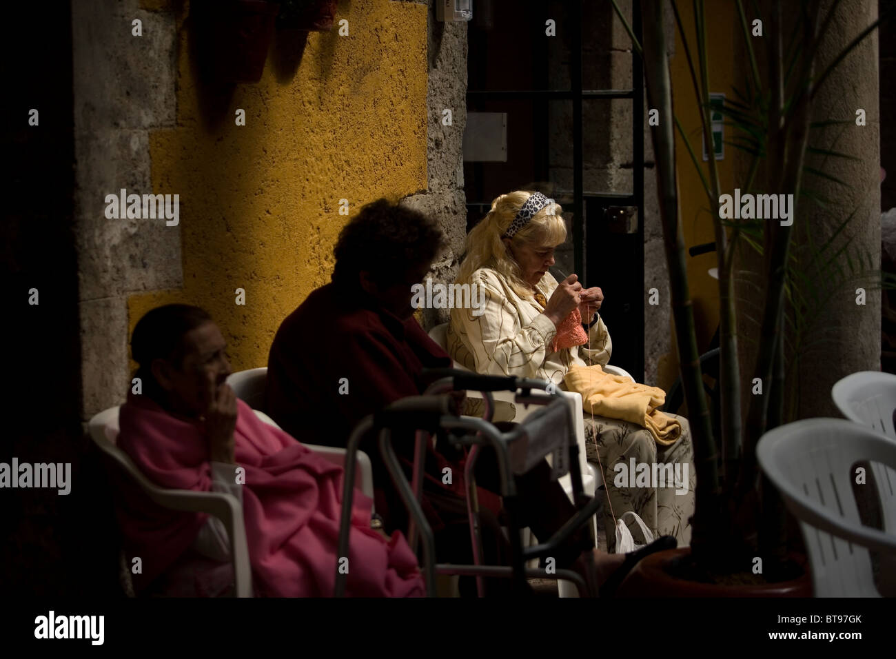 Alma Arjona, 62, right, knits as she sits with other women in Our Lady of Guadalupe Home for the Elderly, Mexico - Stock Image