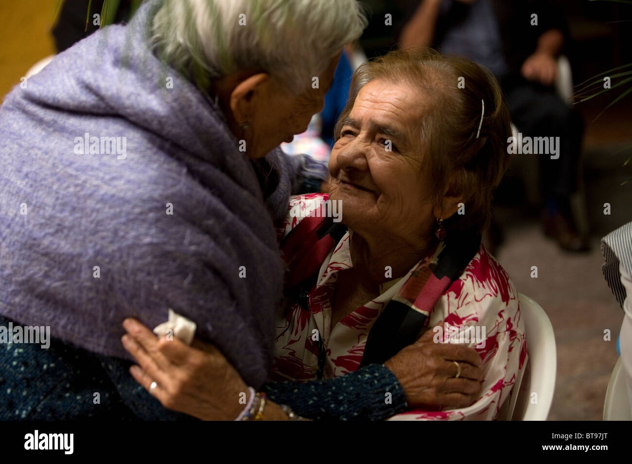A Vicentine volunteer, left, hugs an elderly woman in Our Lady of Guadalupe Home for the Elderly, Mexico City. - Stock Image