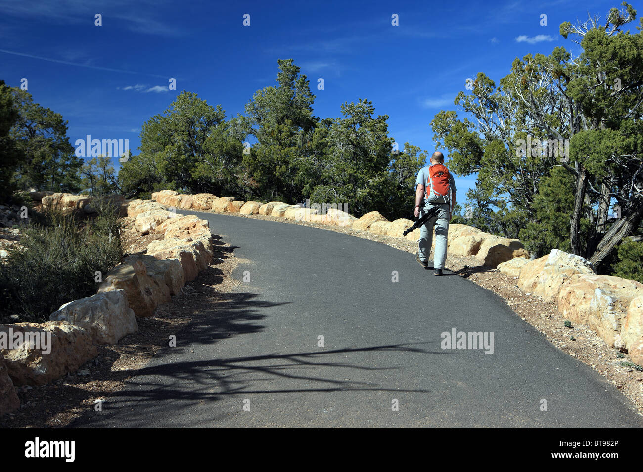 Man walking on the path round the South rim of the Grand Canyon National Park - Stock Image
