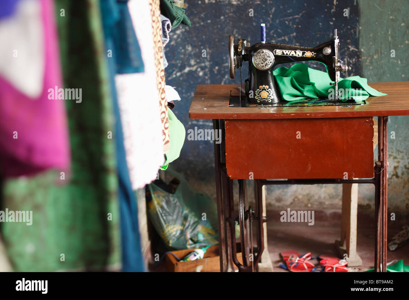 An Antique Sewing Machine Next to a Wall of Handmade Clothing.  Horizontal orientation, full color, shallow depth - Stock Image
