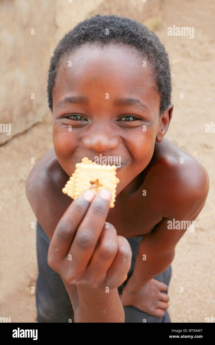 Malawi Boy smiling with Cookies - Stock Image