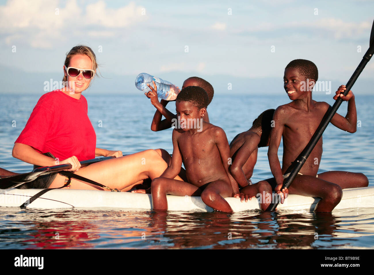 Traveller on a Kayak in Lake Malawi with local children - Stock Image