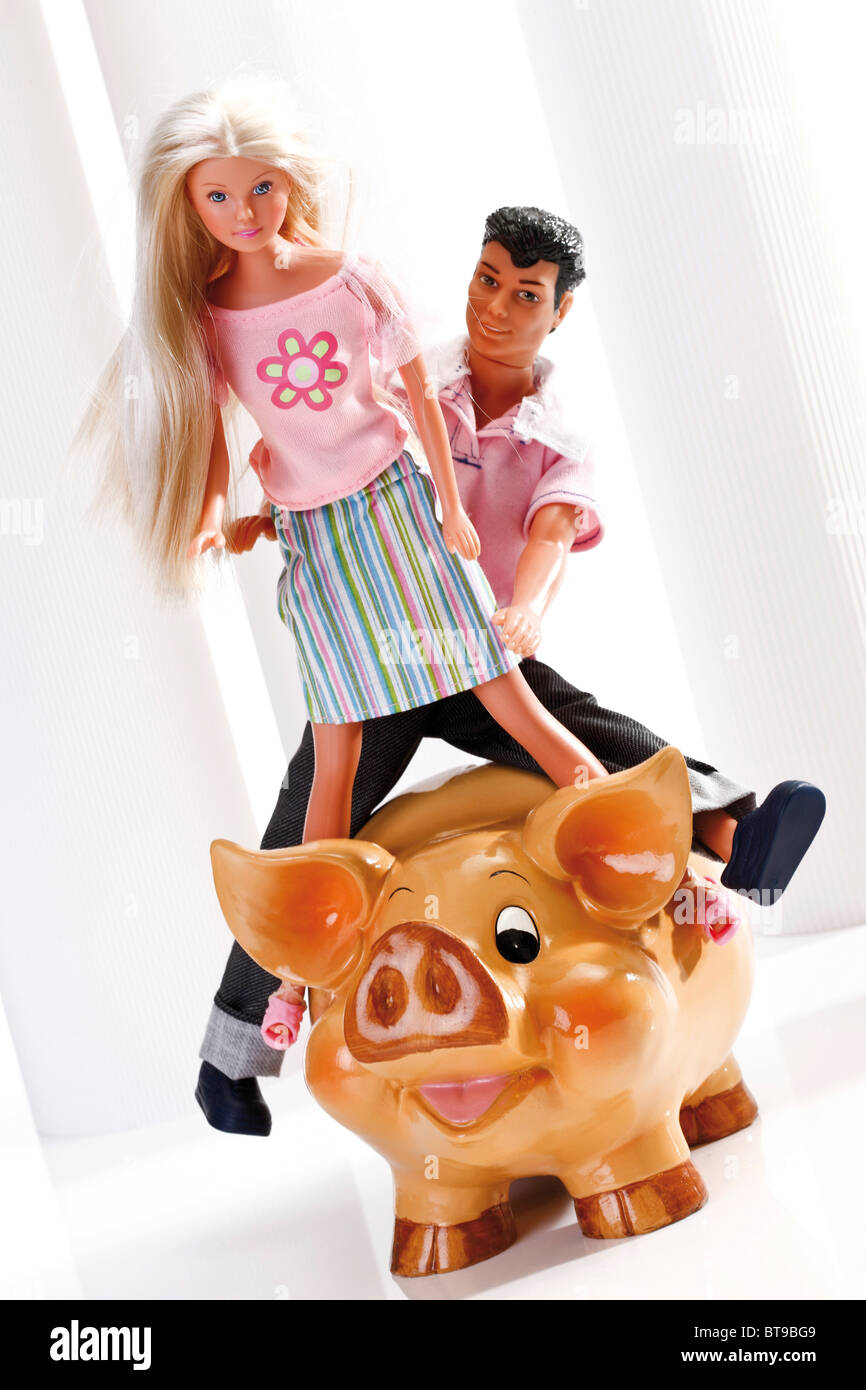 Young couple on a piggy bank, dolls, figurines, a symbolic image for saving for the future - Stock Image
