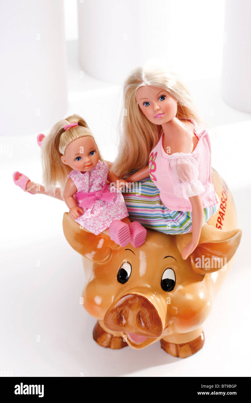 Young mother with daughter on a piggy bank, dolls, figurines, a symbolic image for saving for the future - Stock Image