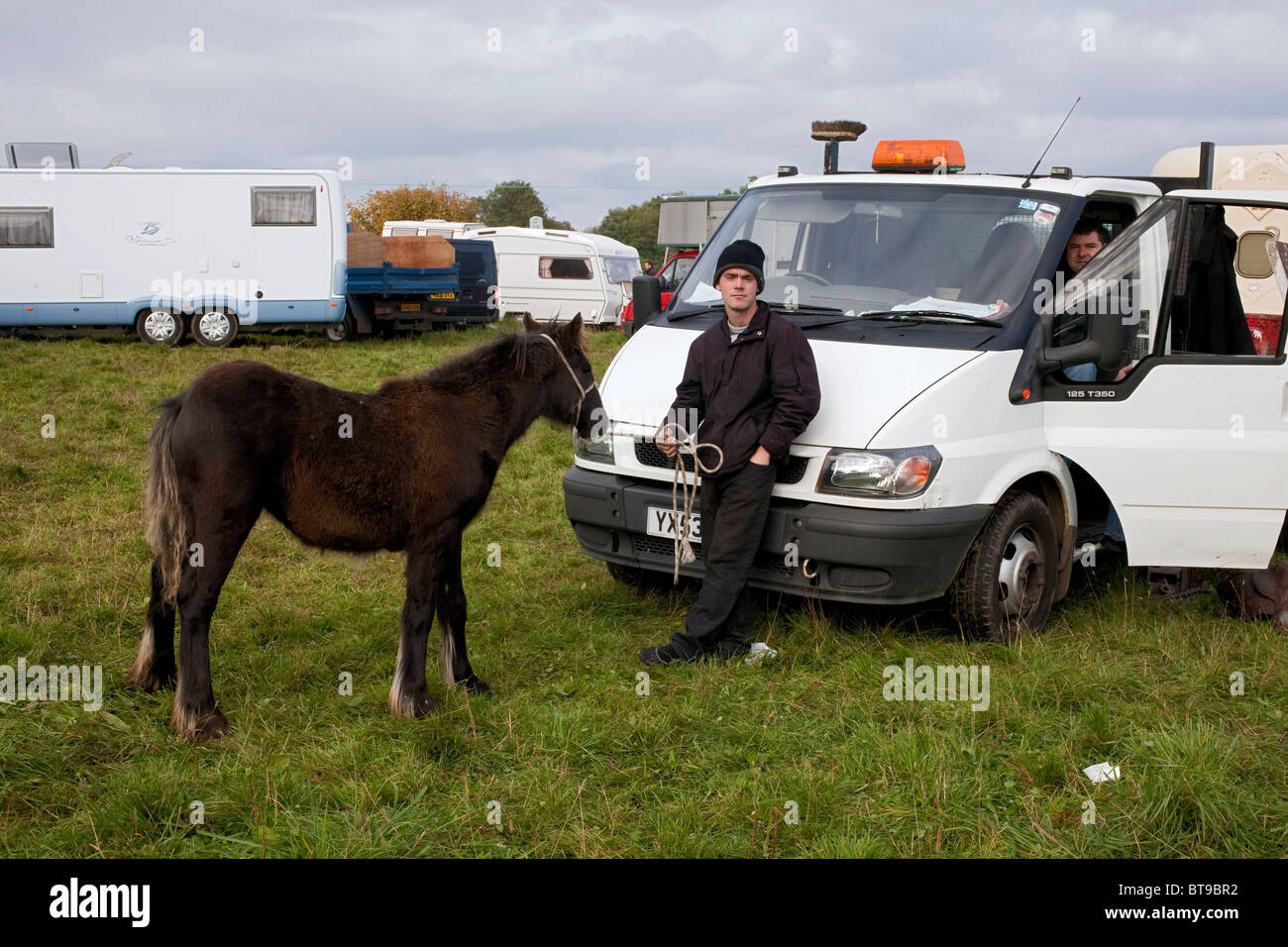 A  young Irish traveller leans on the bonnet of his white pick up truck holding his small pony at Stow Horse Fair. - Stock Image