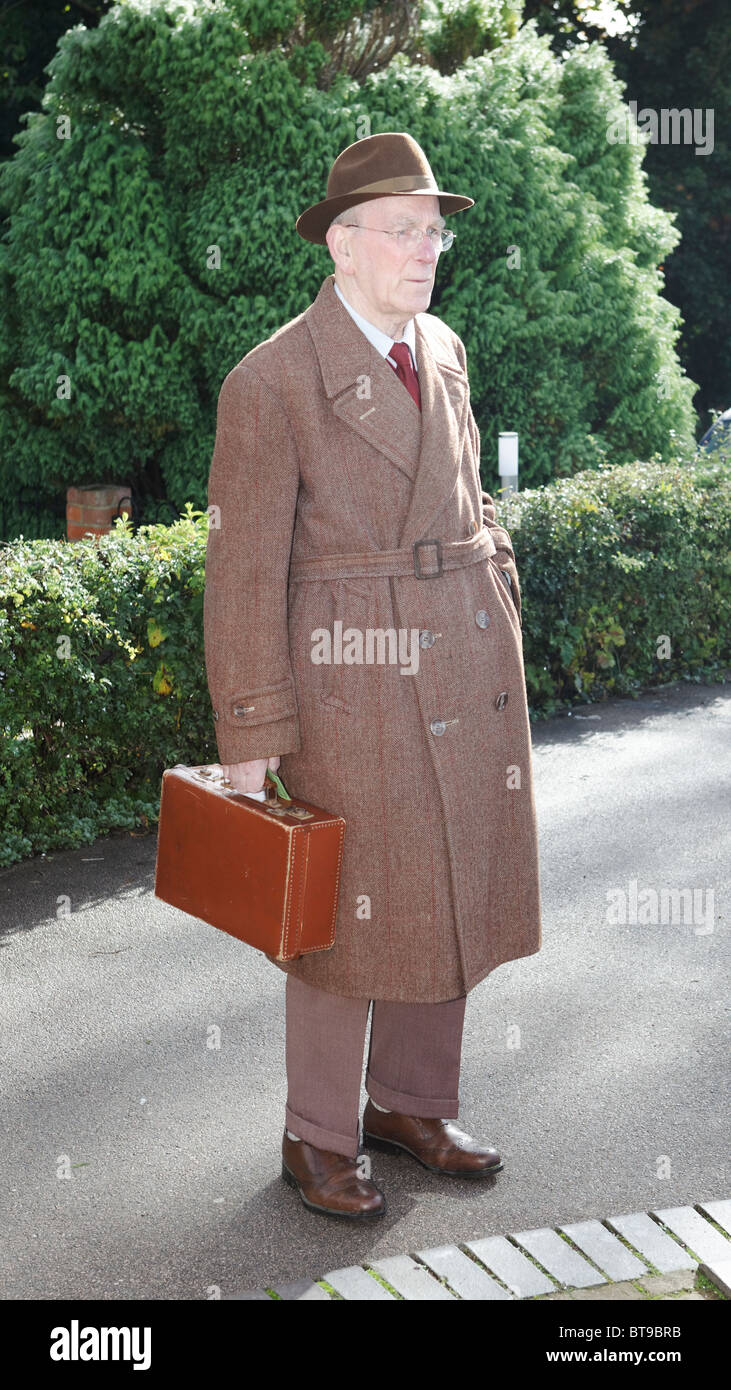 37051dbd1fcba Man Attired in 1940s Style Fedora   Double Breasted Over Coat with Brown  Suitcase