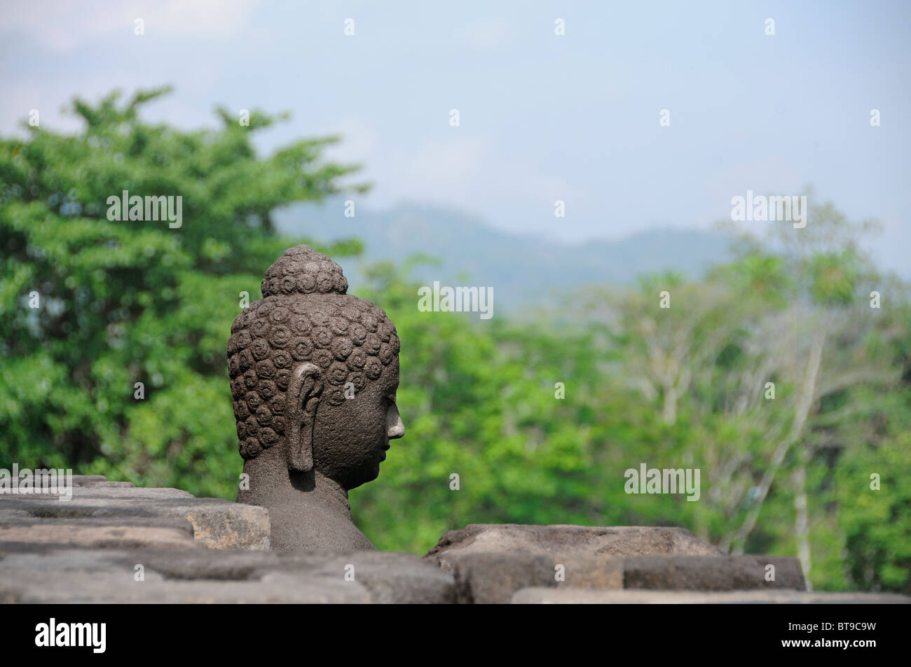 Buddha figure looking over a valley from a dismantled stupa, Borobudur temple, Yogyakarta, Java, Indonesia, Southeast - Stock Image
