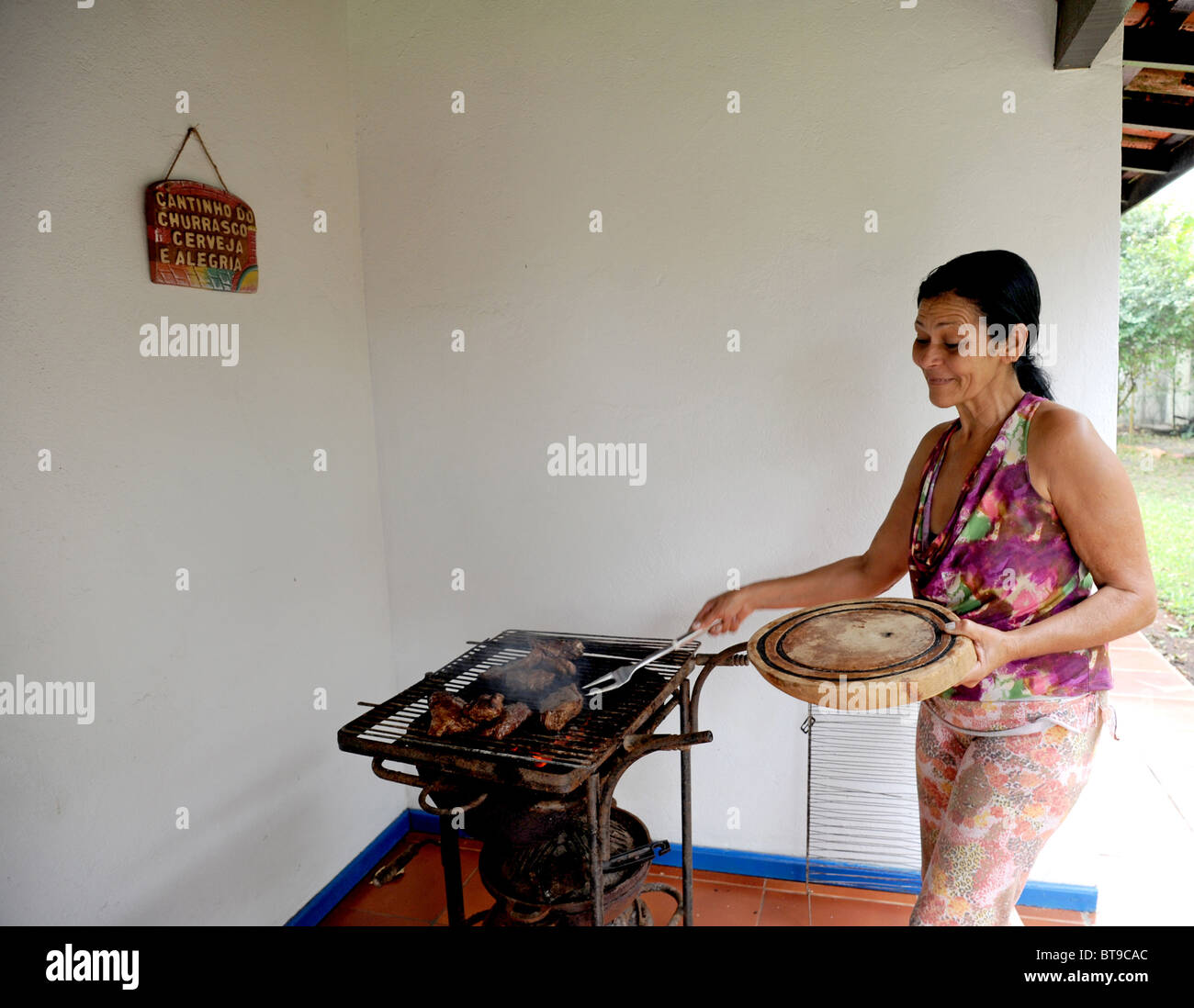 An old Brazilian housekeeper cooks on an outdoor barbecue Stock Photo