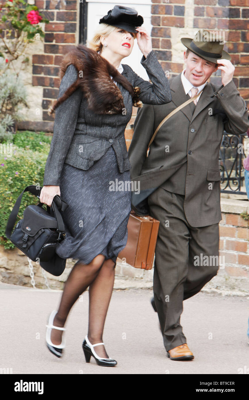 583564fb661 Windy Day for 1940s Woman in Fur Stoal   Husband in Fedora - Reenactors -  Stock