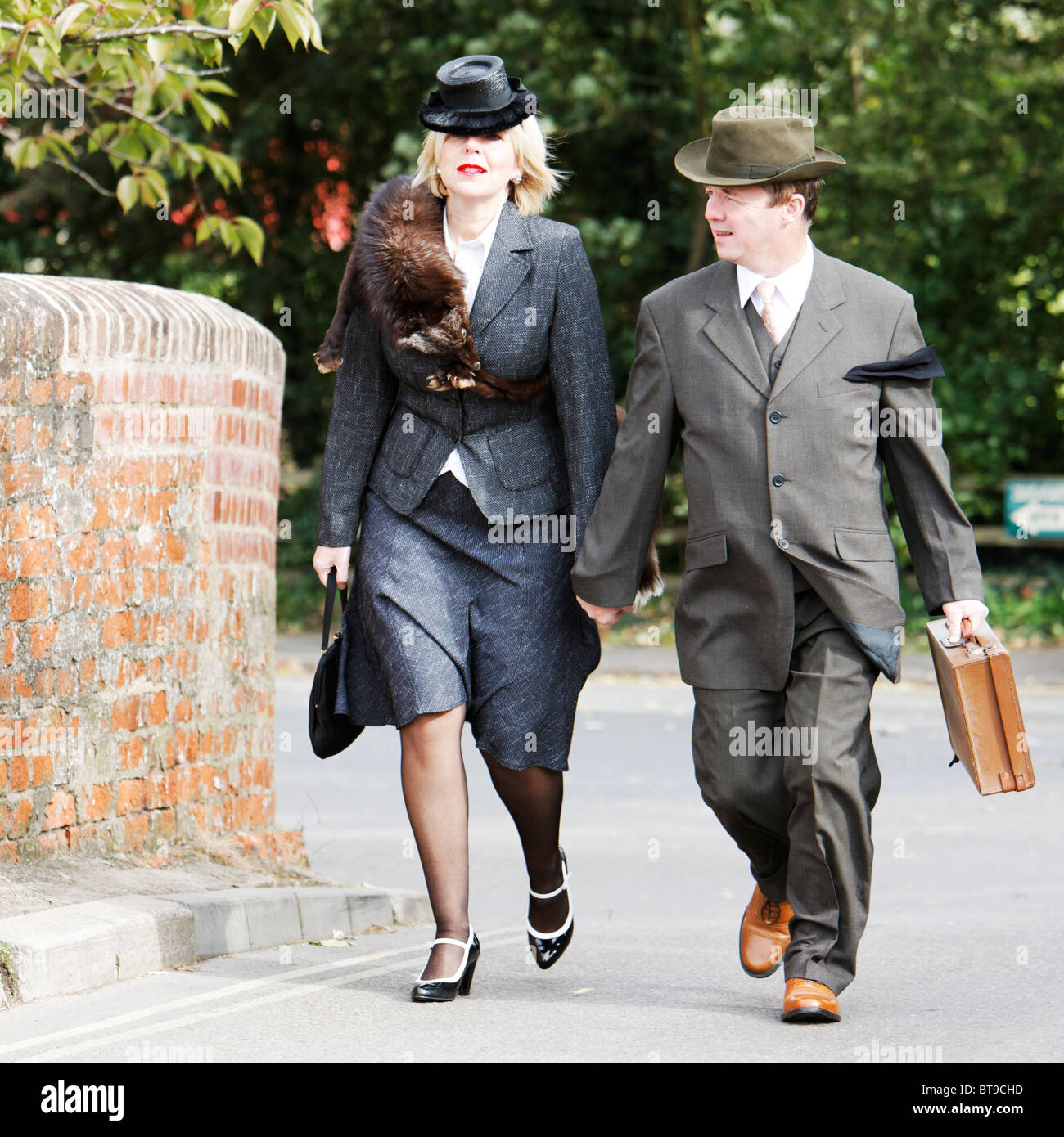 facf73f0333 Windy Day for 1940s Woman in Fur Stoal   Husband in Fedora - Stock Image