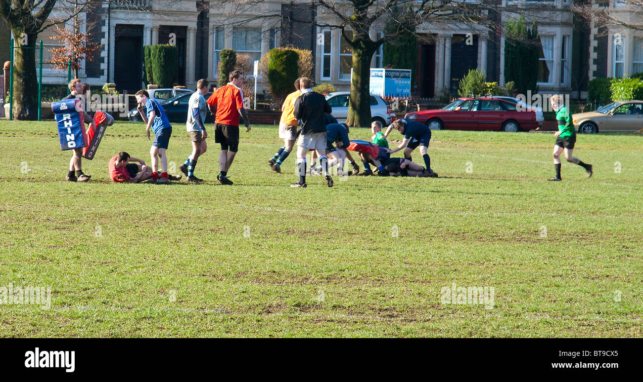 College rugby players practising tackling and passing on Roath Park recreation ground Cardiff UK GB Stock Photo