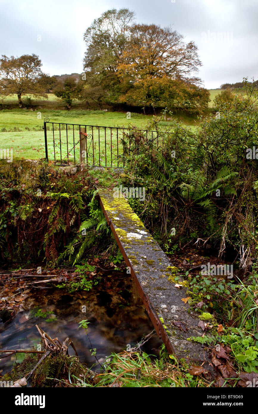 A concrete foot bridge over a moorland stream provides a useful, if rather hazardous crossing point. - Stock Image
