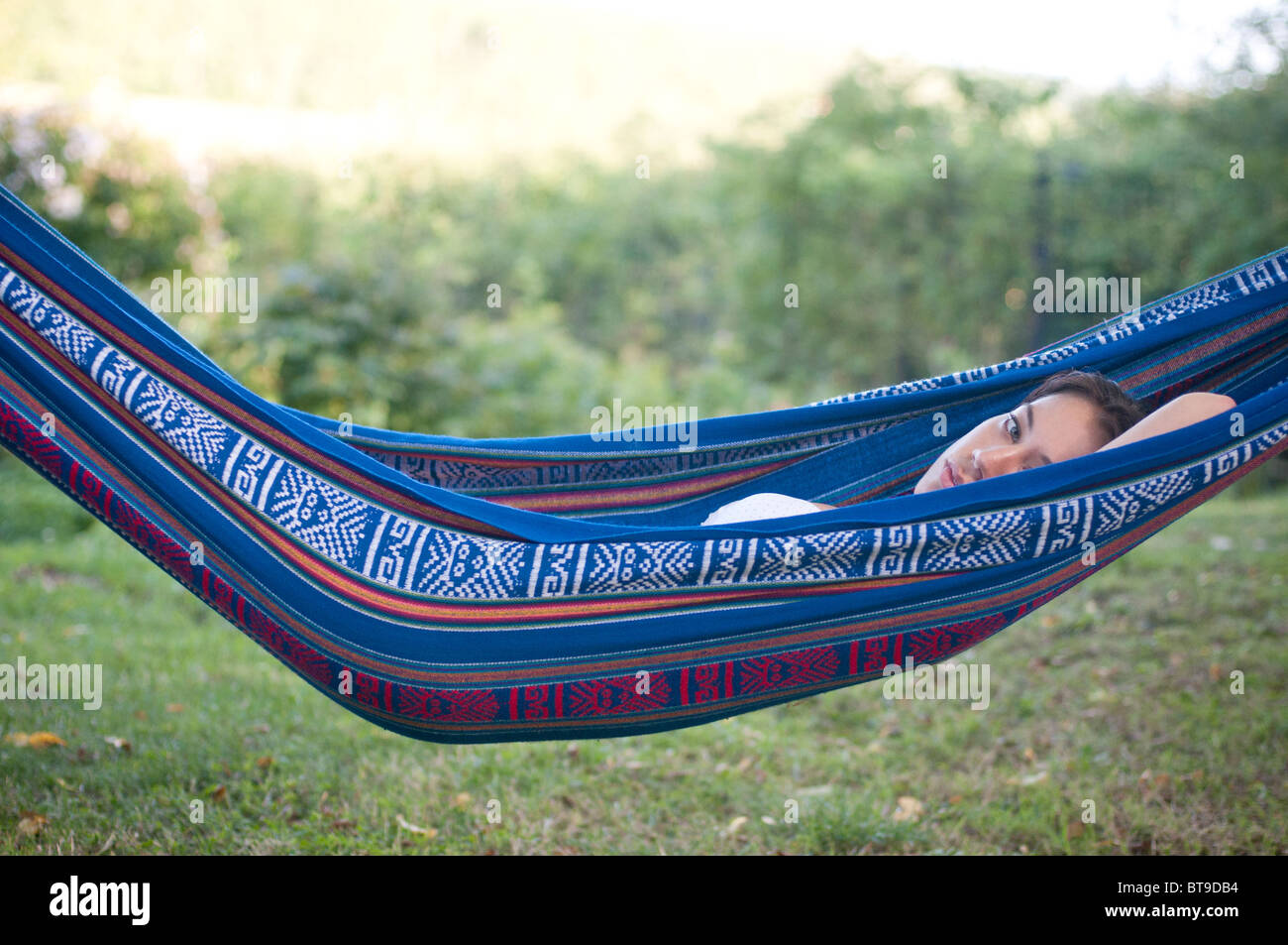 A young woman lying in a hammock in a garden - Stock Image