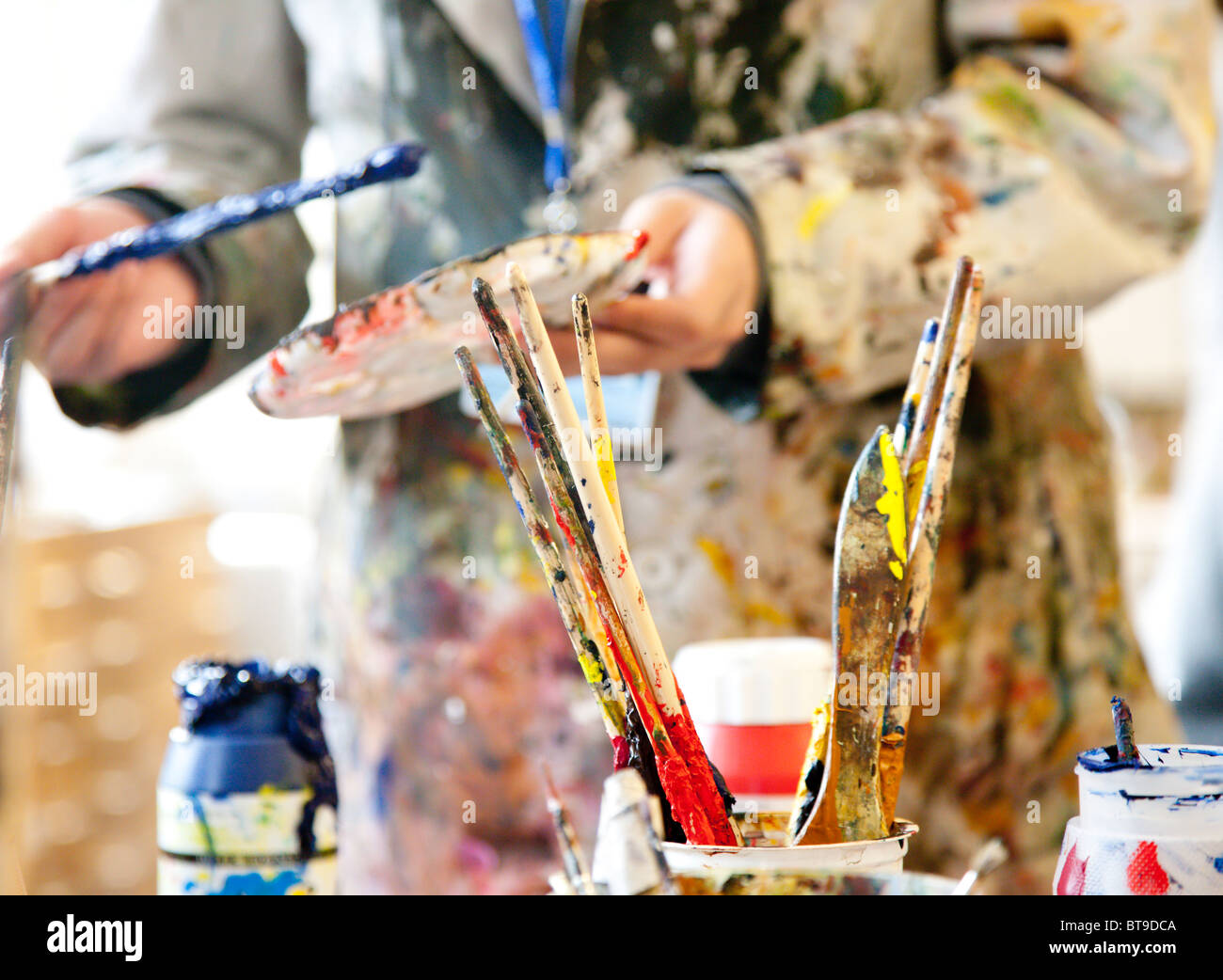 Paint brushes and artist in a paint spattered white coat, differential focus - Stock Image