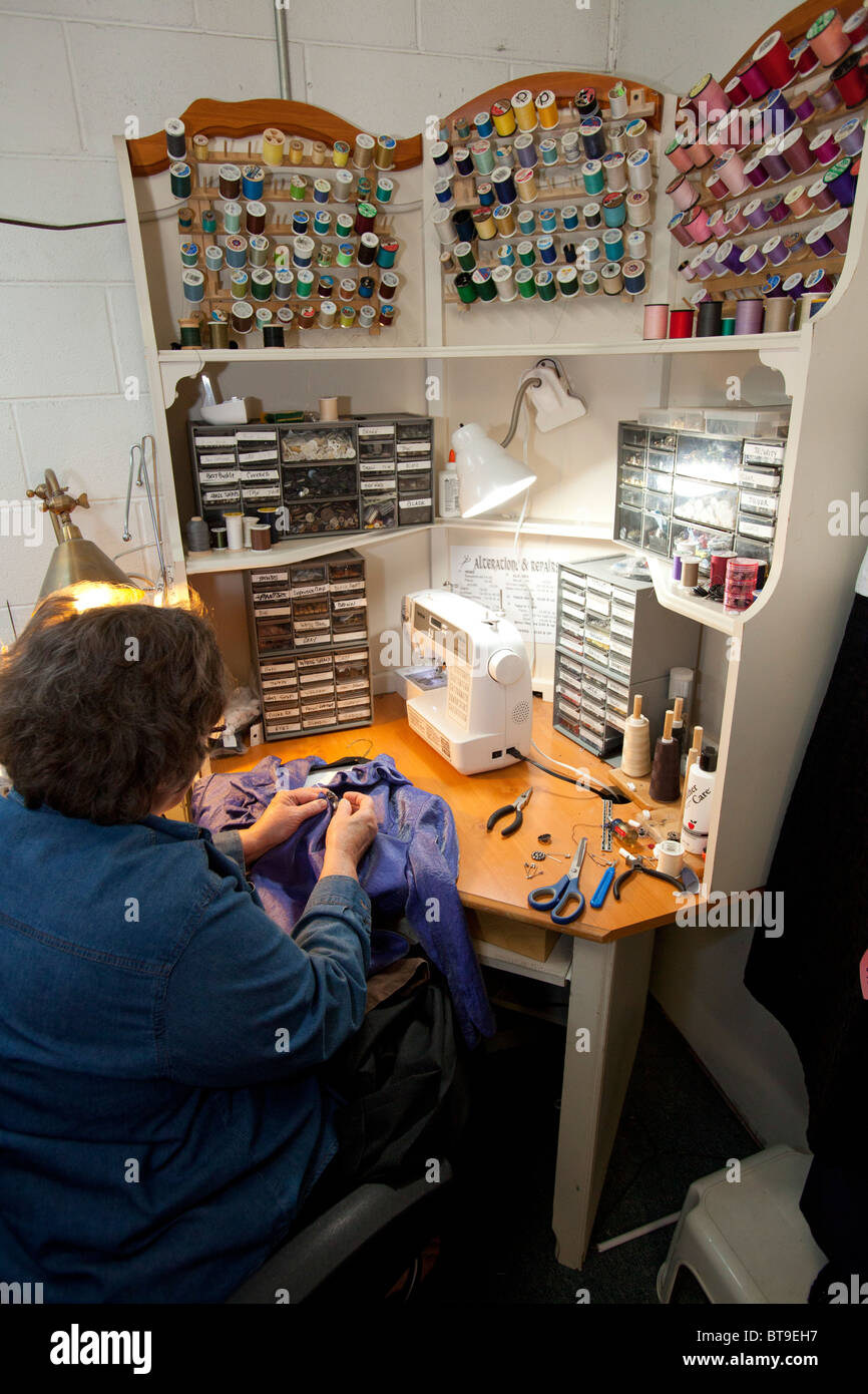 Broomfield, Colorado - Mary Kay Valencia, owner of Lionheart Cleaners, mends a customer's garment. - Stock Image