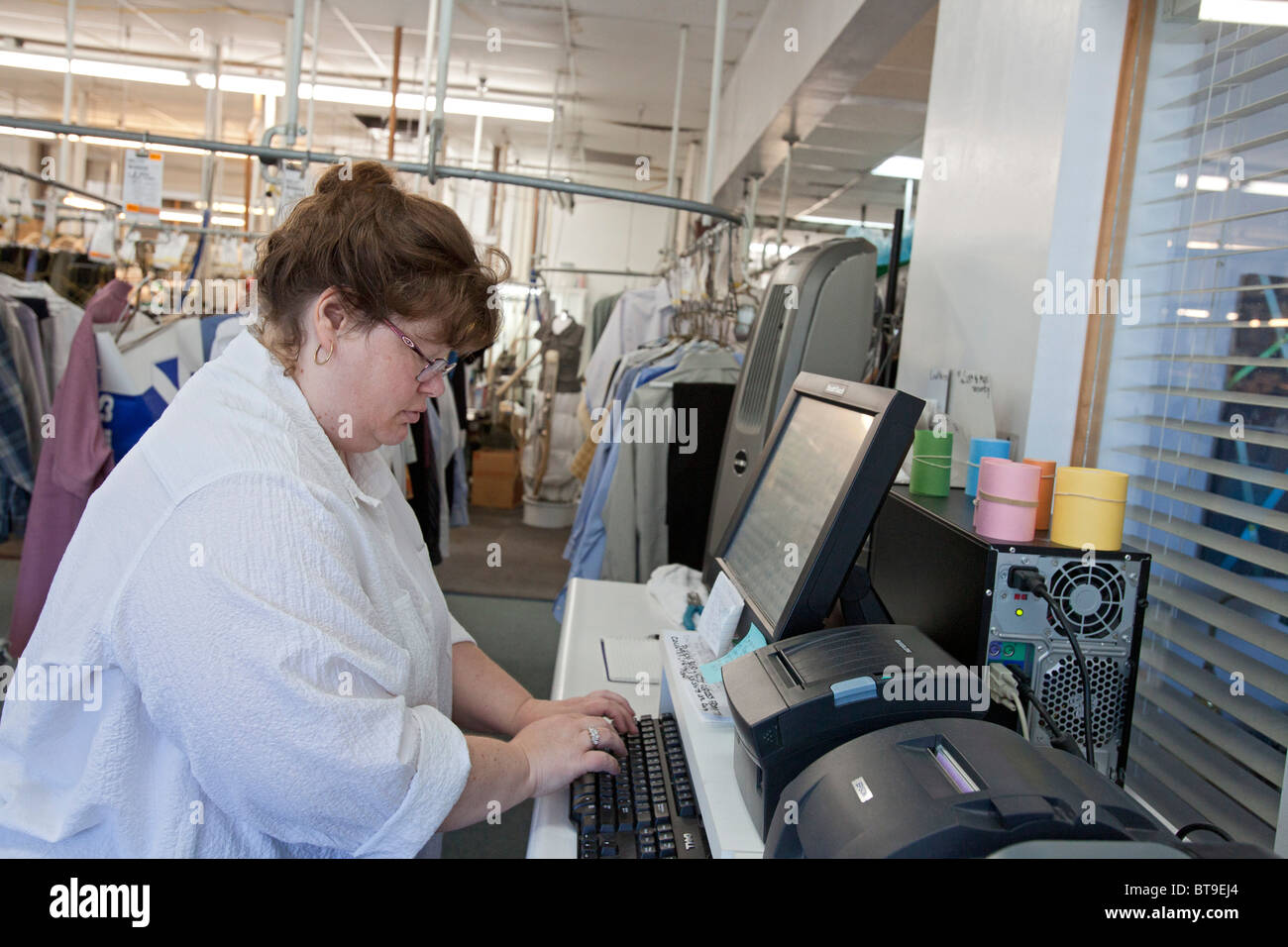 Worker Enters Data on Computer at Dry Cleaning Firm - Stock Image