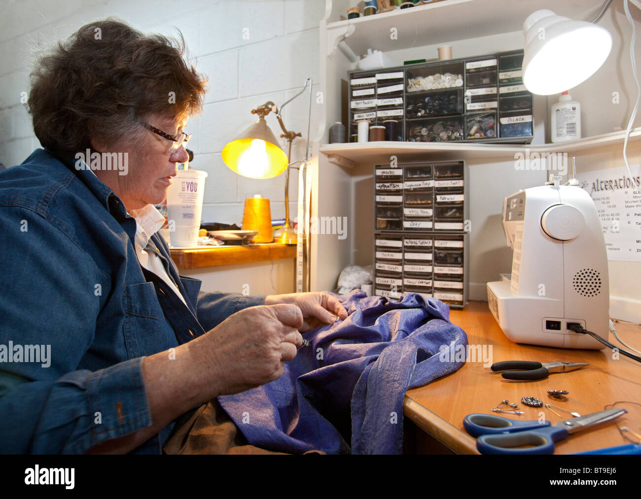 Broomfield, Colorado - Mary Kay Valencia, owner of Lionheart Cleaners, makes alterations on a customer's garment. - Stock Image