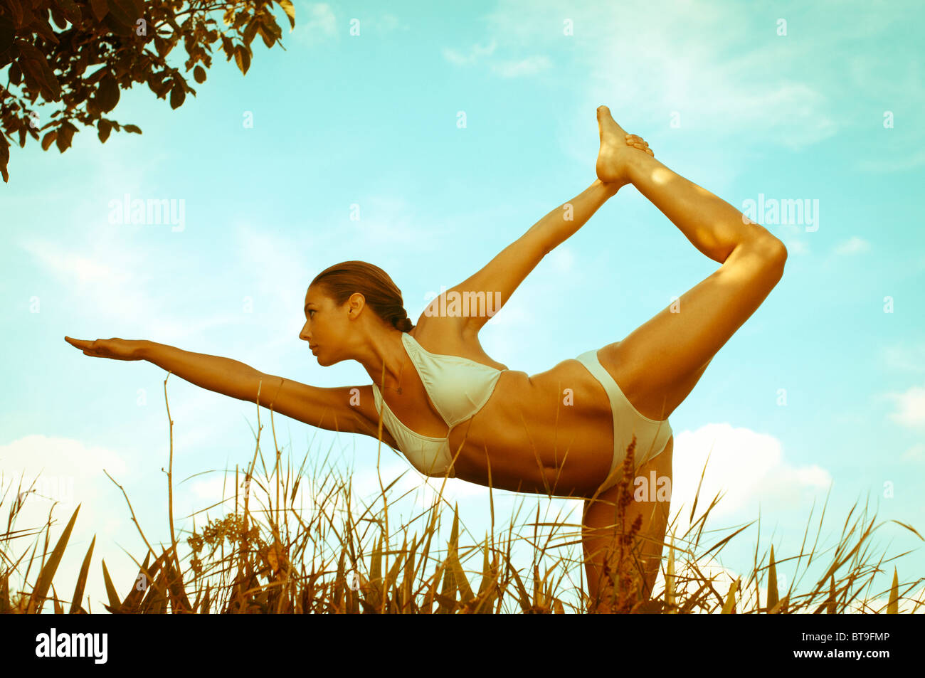 A young woman doing yoga outdoors - Stock Image