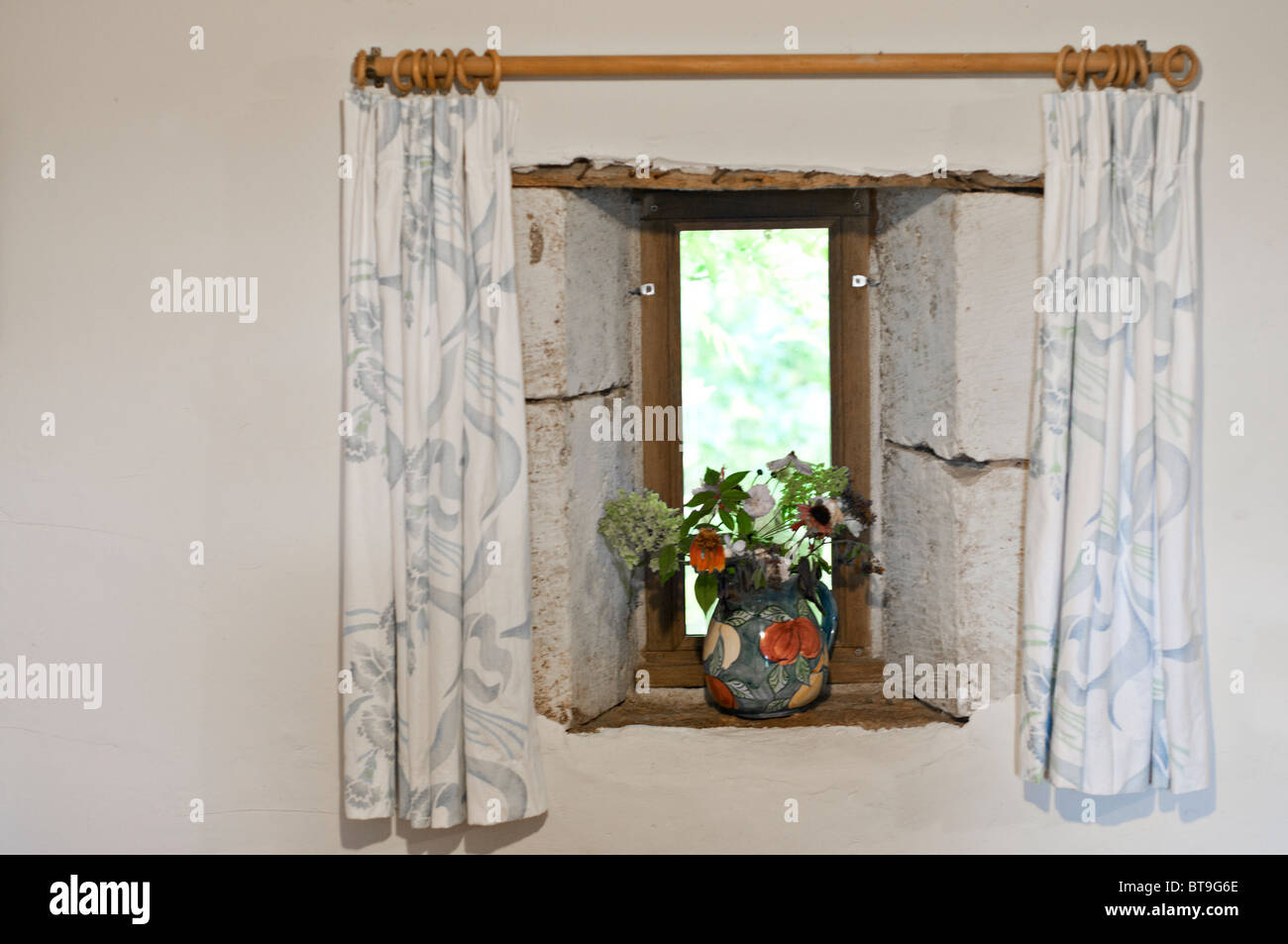 A window with curtains and a vase of flowers - Stock Image