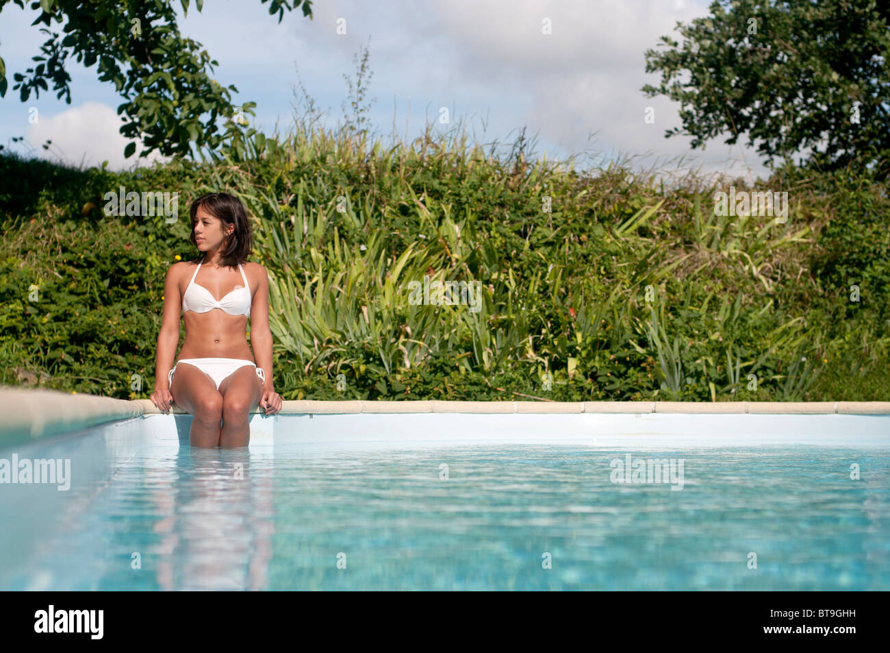A woman sitting by an outdoor swimming pool, legs in the water - Stock Image