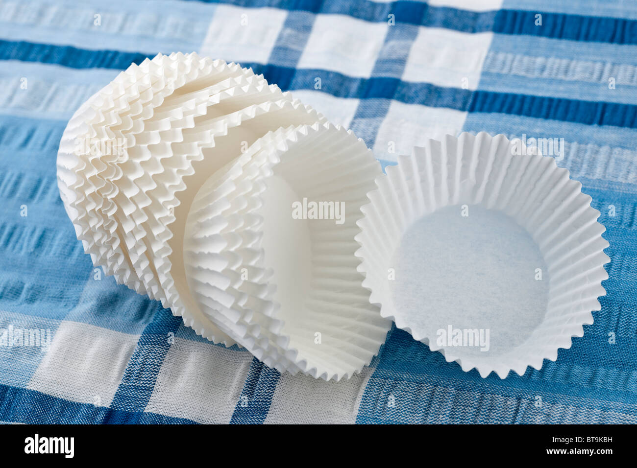 White pastry cases on a blue tablecloth - Stock Image