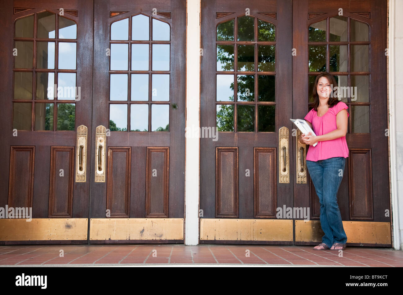 Female high school student holding books and standing at front door of school. - Stock Image