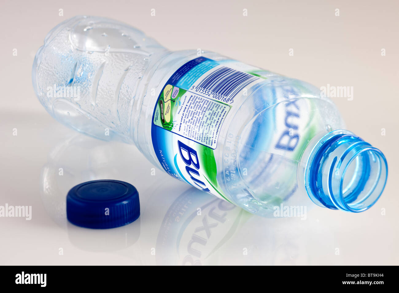 Empty plastic bottle of drinking water and blue screw top - Stock Image