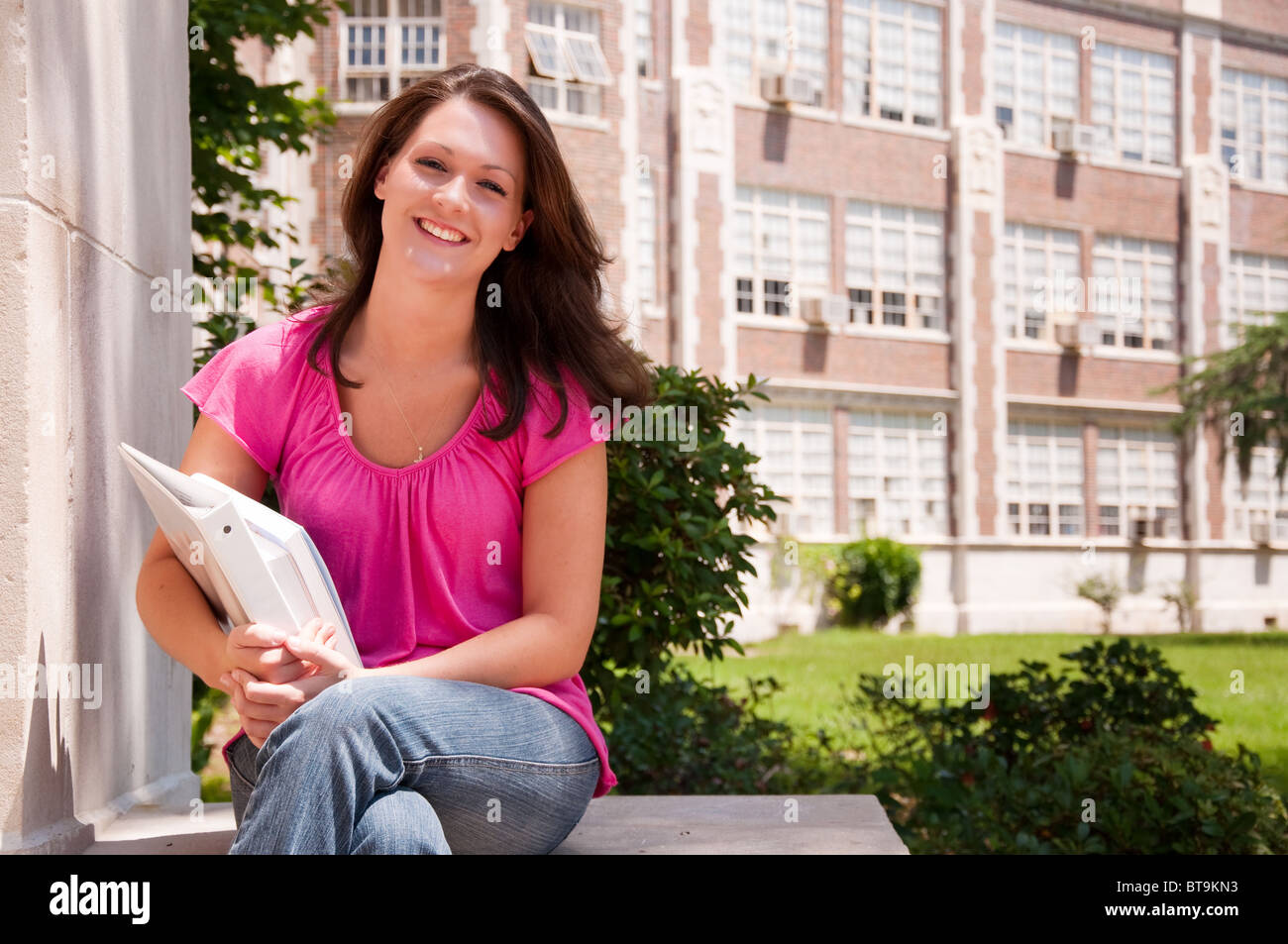 Female high school student seated with books in hand at school. - Stock Image