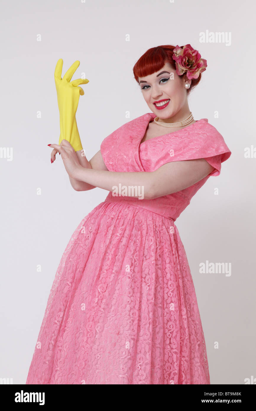 1950s housewife putting on a rubber glove - Stock Image