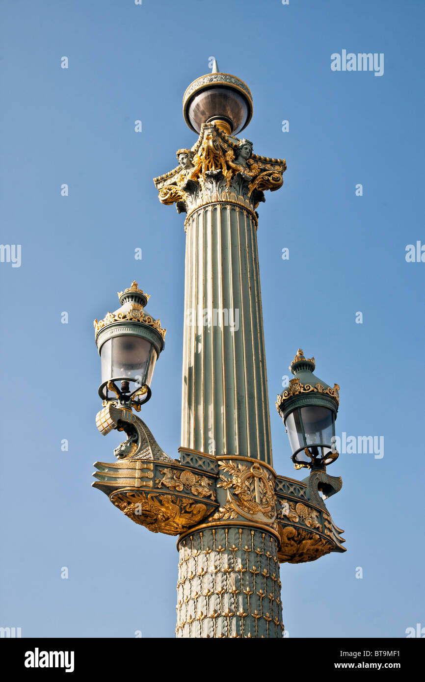 elegant beautifully maintained decorative Beaux Arts gilded French street lamp against clear blue sky Place de la Stock Photo