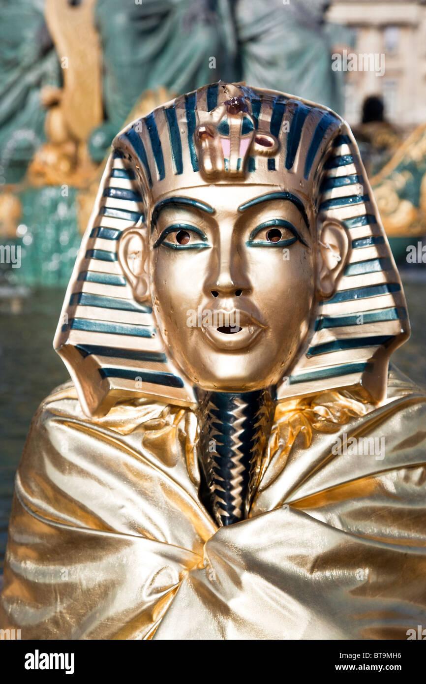 head & shoulders of living statue mime standing in Place de la Concorde Paris wearing gilded King Tut or Sphinx - Stock Image